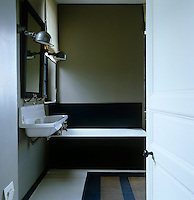 This contemporary bathroom has a beige and dark grey colour scheme and the washbasin came from a local school