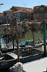 Fishing nets hanging from wooden poles above boats in residential area of Venice.