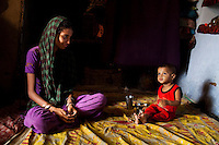 Sadma Khan, 19, sits with her 18 month old son as he eats some snacks in her mother's one-room house which she shares with 5 other family members in a slum area of Tonk, Rajasthan, India, on 19th June 2012. She was married at 17 years old to Waseem Khan, also underaged at the time of their wedding. The couple have an 18 month old baby and Sadma is now 3 months pregnant with her 2nd child and plans to use contraceptives after this pregnancy. She lives with her mother since Waseem works in another district and she can't take care of her children on her own. Photo by Suzanne Lee for Save The Children UK