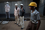 Li Qi (2nd from left), a motion engineer from SEPCO, operating a crane at the plant site and directing nearby Indian workers at the construction site of the Adani Power plant of 4620 MW capacity in Mundra port industrial city of Gujarat, India. Indian power companies have handed out dozens of major contracts to Chinese firms since 2008. Adani Power Ltd have built elaborate Chinatowns to accommodate Chinese workers, complete with Chinese chefs, ping pong tables and Chinese television. Chinese companies now supply equipment for about 25% of the 80,000 megawatts in new capacity.