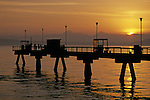Silhouetted pier with people fishing off pier at sunset on Puget sound with Olympic mountains Edmonds Washington State USA