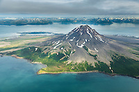 Aerial view of the active Mt. Augustine volcano, situated just off the Alaska Peninsula on Alaska's southwest coast, Aleutian mountain range in the distance.