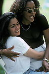 Multi racial - African-American and white lesbian couple, hugging, laughting, in Central Park during Gay & Lesbian Pride Weekend