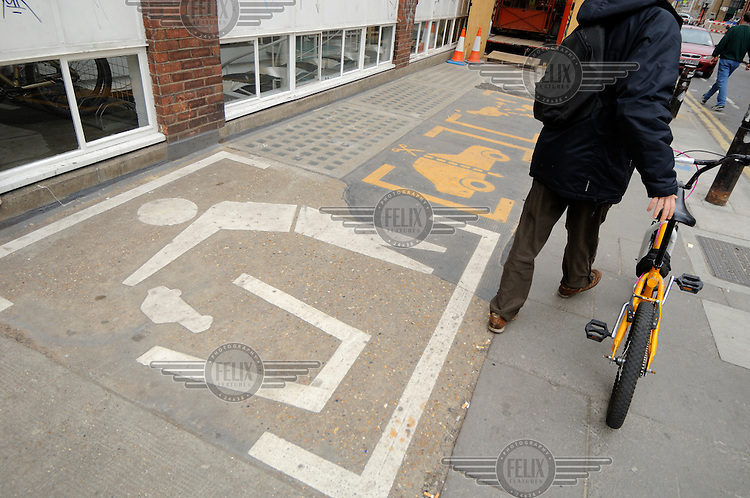 Anti-car stencils on the pavement outside a fashionable design studio close to Spitalfields in East London.