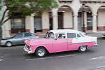 Havana, Cuba; a classic pink and white 1955 Chevy Bel Air driving along the Paseo de Marti past the Saratoga Hotel