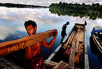 """Loggers unload a boat of Greenheart and purpleheart timber at Rockstone landing, guyana.  They had to bail the boat all night to keep it afloat.  These amerindians are called """"pokenockers"""" because they poke around here, knock around there trying to make a little bit of money.  They travel the trails that trace the interior of Guyana all the way to the """"back door"""" of Brazil."""