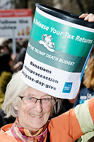 A woman carries a bucket for donations to Mass Peace Action as people gather in Cambridge Common for a Tax Day protest near Harvard Square in Cambridge, Mass., on Sat., April 15, 2017. The demonstrators called for President Donald Trump to release his tax returns. Trump refused to release his tax returns during the 2016 presidential campaign, in contrast to all previous major party presidential candidates, and continues to refuse to release them. The protest was part of a larger movement nationwide called Tax March.