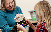 NWA Democrat-Gazette/DAVID GOTTSCHALK  Sherry Rodgers (left), children's librarian for the Washington County Library System, holds a raccoon hand puppet Wednesday, February 15, 2017, as Lauren Remington, 7, ties it's shoelaces during the Getting Dressed themed Spring Story Time at the Lincoln Public Library. Spring Story Time for the library system runs through May 19 presenting programs for ages three and up.