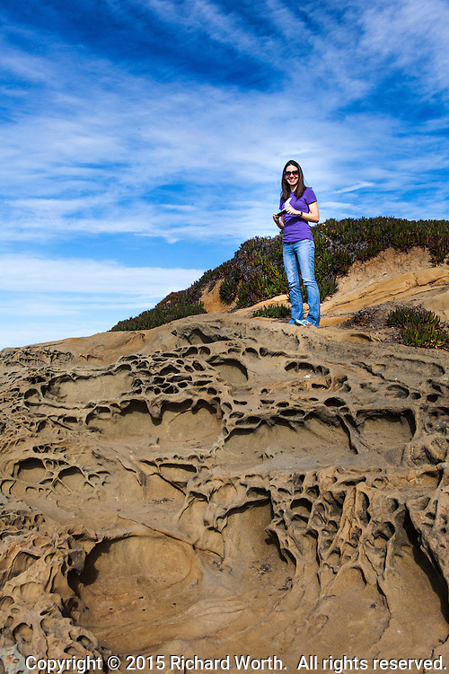 A young woman, Kacie, standing under a blue, cloud-streaked sky on sandstone pockmarked with  tafoni formations at Bean Hollow State Park on the California coast south of San Francisco.