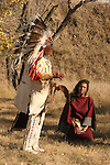 A Native American Indian telling stories during the fall with his daughter kneeling and listening