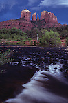 Cathedral Rocks from Oak Creek Canyon Red Rock Crossing with storm clouds over rock formations and small waterfall in foreground, Sedona, Arizona State USA