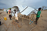 A family puts the tent fabric on a structure they built in a camp for almost 500 internally displaced people located at the St. Vincent de Paul Catholic parish on the edge of Juba, the capital of South Sudan. The families here fled fighting that broke out in December 2013. More than 700,000 people have been internally displaced in the first three months.