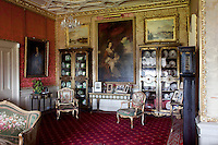 An 18th century portrait in the drawing room, flanked by two glazed china cabinets and needlepoint upholstered armchairs