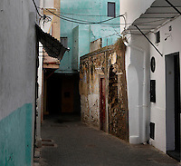 Medina, Tangier, Morocco, pictured on December 27, 2009. A narrow street in the Old Town where clean white and turquoise walls contrast with one old wall whose stonework is bare. Tangier, the 'White City', gateway to North Africa, a port on the Straits of Gibraltar where the Mediterranean meets the Atlantic is an ancient city where many cultures, Phoenicians, Berbers, Portuguese and Spaniards have all left their mark. With its medina, palace and position overlooking two seas the city is now being developed as a tourist attraction and modern port. Picture by Manuel Cohen