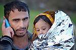 A refugee holds his daughter as he informs his family that they have arrived safely on a beach near Molyvos, on the Greek island of Lesbos, on October 30, 2015, after they crossed the Aegean Sea from Turkey in a small overcrowded boat. They were received in Greece by local and international volunteers, then proceeded on their way toward western Europe.