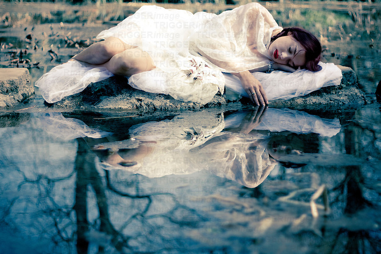 Young woman wearing a white summer dress relaxing next to water with reflection in summer