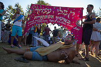 Israeli men lay on the grass as he participate in the annual gay pride parade in Jerusalem, Thursday, Aug. 1, 2013.  Photo by Oren Nahshon