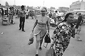 An Uzbek woman, in floral dress, and a Soviet woman struggle through wind and dust in Chorsu Bazaar, a market in the old Silk Road trading route city of Tashkent, Uzbekistan.
