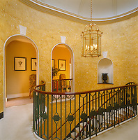 A graceful curved banister with painted wrought-iron uprights is a feature of the landing at the top of the main staircase