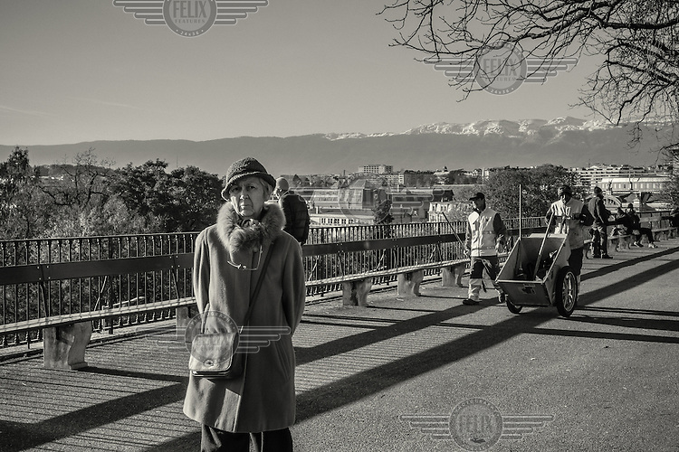 A woman walks in a park. Behind her are two men working for the city's cleaning services.