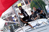 Black Match crew members during a spinnaker hoist on day 3 of Match Race Germany 2010. World Match Racing Tour. Langenargen, Germany. 22 May 2010. Photo: Gareth Cooke/Subzero Images/WMRT