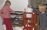 Kinder füllen teilweise eingerichtetes Becken mit Wasser auf