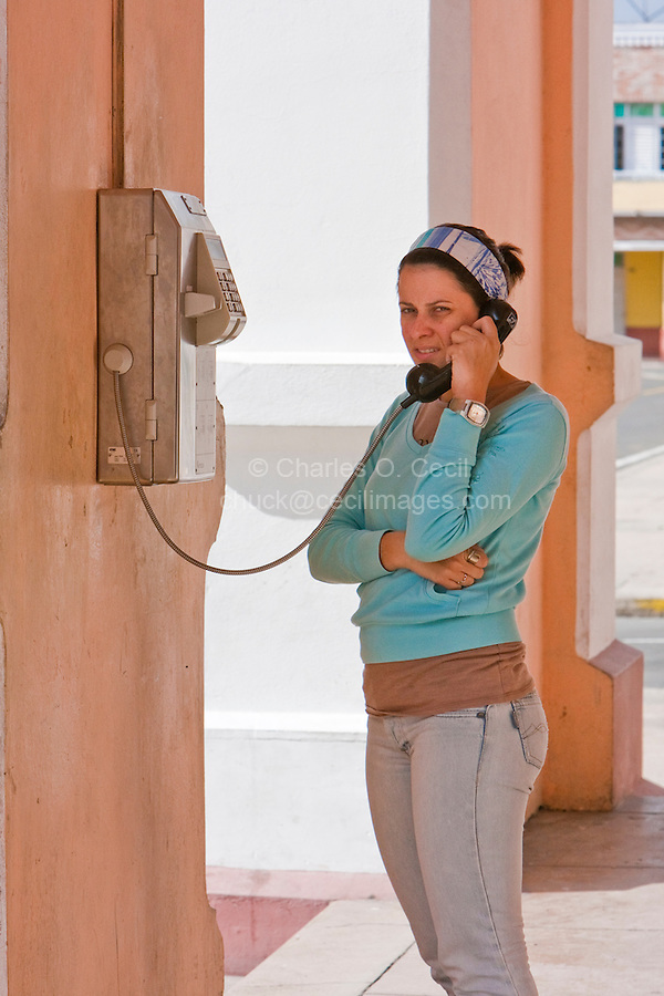 Cuba, Cienfuegos.  Cuban Lady Using a Public Pay Phone.
