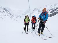Skiløpere på Langfjordjøkelen. Stakene i isen måler endring i breens størrelse. --- Skiers on the glacier Langfjordjøkelen.