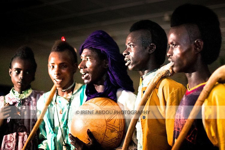 """In the town of Djibo in northern Burkina Faso, young """"doohoobe"""" (people who sing """"doohaali"""") dance in traditional fashion. The men and women each form a line facing each other, rhythmically shuffling towards and then away from each other. The women clap their hands and sing as the men """"dooho,"""" or sing a distinct, deep rhythmic chant. The man in the purple turban plays a calabash (a form of drum), as the other men hold """"cabbi,"""" sticks which are used when herding cattle. """"Doohaali"""" is a distinct form of music practiced only by the Fulani in Djelgooji, a particular area of Burkina Faso. The young men in this image are the winners of a regional music and arts competition, going on to perform at Burkina Faso's 2010 """"Semaine Nationale de la Culture"""" (SNC) in Bobo-Dioulasso."""