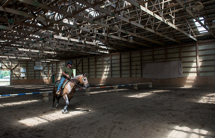 An instructor works with a horse in the indoor ring at the Horse Park of OUS.