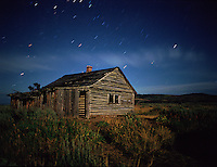An old settler's cabin is illuminated by the moon, while the Wyoming night sky shows its stuff.