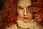 Close-up portrait of female youth with freckles and red curly hair holding an autumn leaf over one eye.