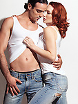 Sensual portrait of a sexy young couple in blue jeans and white tank tops on white background