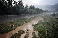 "A man crosses one of the main channels that makes up the Dujiangyan Irrigation System. The system is regarded as an ""ancient Chinese engineering marvel."" By naturally channeling water from the Min River during times of flood, the irrigation system served to protect the local area from flooding and provide water to the Chengdu basin. Sichuan Province. 2010"