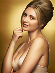 Beautiful young glamorous woman wearing in underwear, closeup beauty portrait in golden colors on shiny gold background