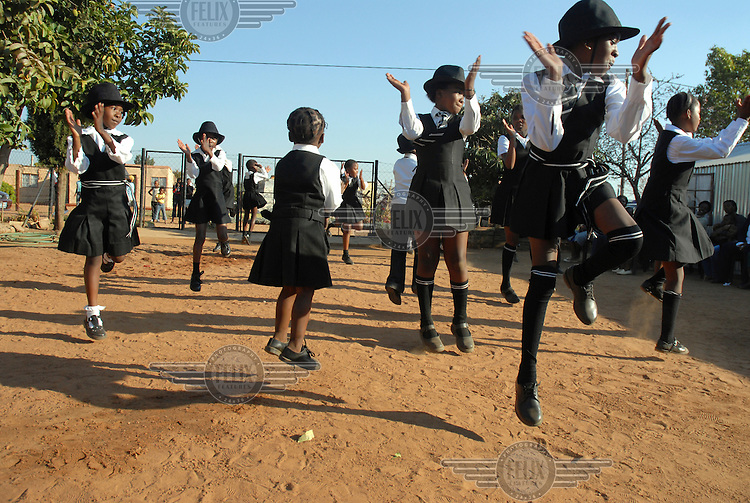 Young girls dance a scene from the South African hit production Sarafina, which is about the 1976 Soweto school uprising, in Soshanguve Township. The children are part of a support and counselling program run by the Leseding Support Centre, which provides services to HIV positive people, orphans and victims of abuse in the community.