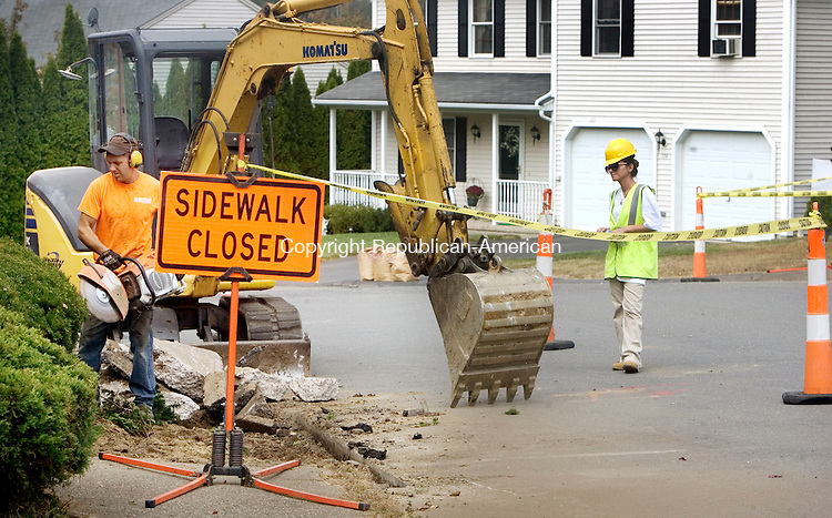 WATERBURY CT. 29 September 2015-092915SV06-From left, Bill Olmstead removes the old sidewalk and Sihama Rizvani keeps traffic moving during a reconstruction of the sidewalks on Lincroft Drive in Waterbury Tuesday. The work is part of a city-paving project. <br /> Steven Valenti Republican-American