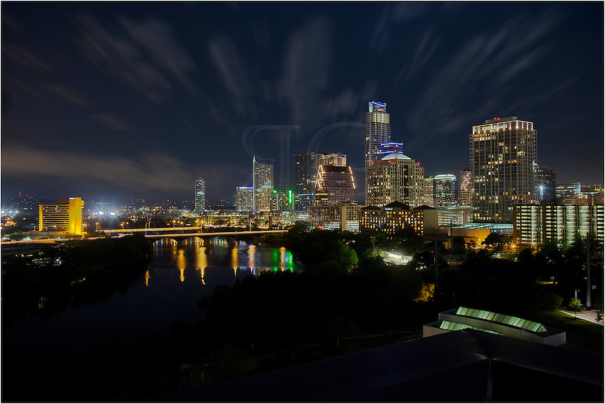 This photograph is a long exposure  of downtown Austin and Lady Bird Lake at night. The Frost Tower is just east (right) of Congress Bridge, adding a nice touch the Austin skyline.