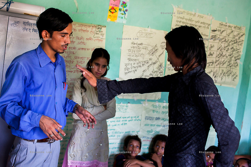 (standing L-R) Safer Society staff Ganesh Bahadur Oli (24), Bhawani Regmi (16) and Chandraseker Shahi (17) do a drama play about refusing underaged arranged marriages at the Kishuri Sachetana Child Club in their activity center in Thahuri Tole, Chhinchu, Surkhet district, Western Nepal, on 1st July 2012. These Child Clubs, supported by the government, Save the Children and their local partner NGO Safer Society, advocate for child rights and against child marriages and use peer support and education to end child marriages and raise awareness. Photo by Suzanne Lee for Save The Children UK
