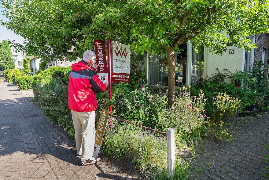 Nederland, Driebergen, 21 mei 2015<br /> Te koop op bord van makelaar wordt verwisseld door 'Verkocht'. Huis verkocht, huizenverkoop trekt aan.<br /> <br /> Foto: Michiel Wijnbergh