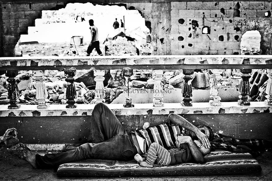 Gaza, Beit Hanoun: Abdel Abu Ouda, fr&egrave;re de Shady, et son fils se reposent dans le salon de leur maison a moitie d&eacute;truite lors des bombardement de l'&eacute;t&eacute;  2014. <br /> <br /> Gaza, Beit Hanoun: Abdel Abu Ouda, Shady's brother, and his son are resting in the living room of their house half destroyed during the bombing of summer 2014.