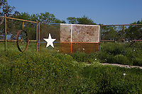 Rural landscape with Texas Flag Design on metal fence gate
