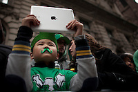 A boy takes pictures of revellers on Fifth Avenue during the 252nd annual St. Patrick's Day Parade in New York City. Photo by Eduardo Munoz Alvarez / VIEWpress.