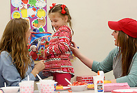 NWA Democrat-Gazette/DAVID GOTTSCHALK  Ruby Seay, 4, laughes as she makes a strawberry shortcake Tuesday, February, 14, 2017, between Jessica Luckett (left), with the Arkansas Support Network, and Ferrin Webb, a senior and Pre-School Teacher at the University of Arkansas Autism Research Clinic, during a Valentines Day Party on the campus in Fayetteville. The pre-school students and alumni students participated in the activities that included making a Valentines Day Ladybug, decorate goodie bags, making a strawberry shortcake and participating in Valentines Day learning activities.