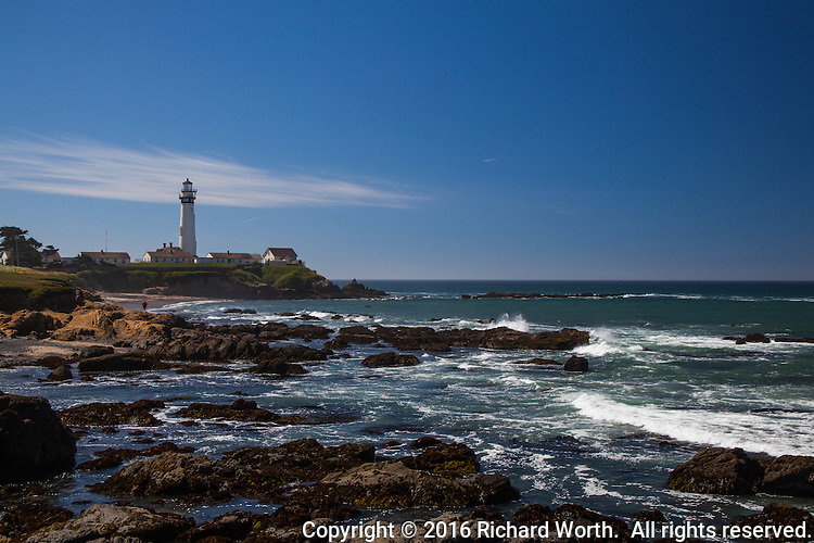 Blue skies with a hint of clouds over Pigeon Point Light Station on the California coast.