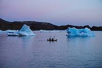 Kayakers in inflatable kayak paddling through icebergs in Kong Oscars Havn, Tasiilaq, Greenland