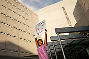 """Leilah Nichols, 8, holds a sign that reads """"Treat Prisoners FairlyÖThe Children Are Watching"""" outside the Durham County Jail while attending a protest with her mother, Nadiah Porter, Friday, May 1, 2015. The demonstators were protesting in solidarity with protestors in Baltimore."""