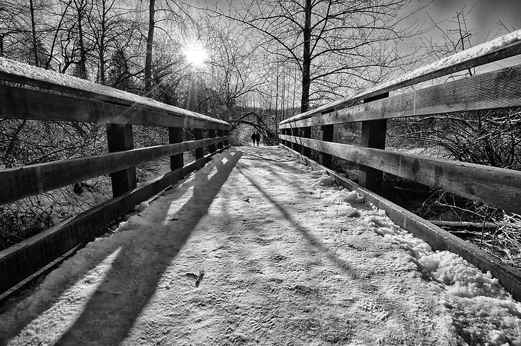 Two people off in the distance on a snow covered bridge with lighrays from sun overhead.