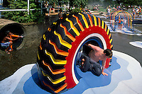 Kids playing at Recycled Tire in Children's Water Park and Playground in Parksville, Vancouver Island, British Columbia, Canada (No Model Release)