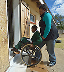 Tarisayi Zhanje pushes her grandson, Hailey Kushaya, into a house where she rents a room in Harare, Zimbabwe. She cares for the 9 year old since his parents died. His appropriately-designed and fitted wheelchair was provided by the Jairos Jiri Association with support from CBM-US.